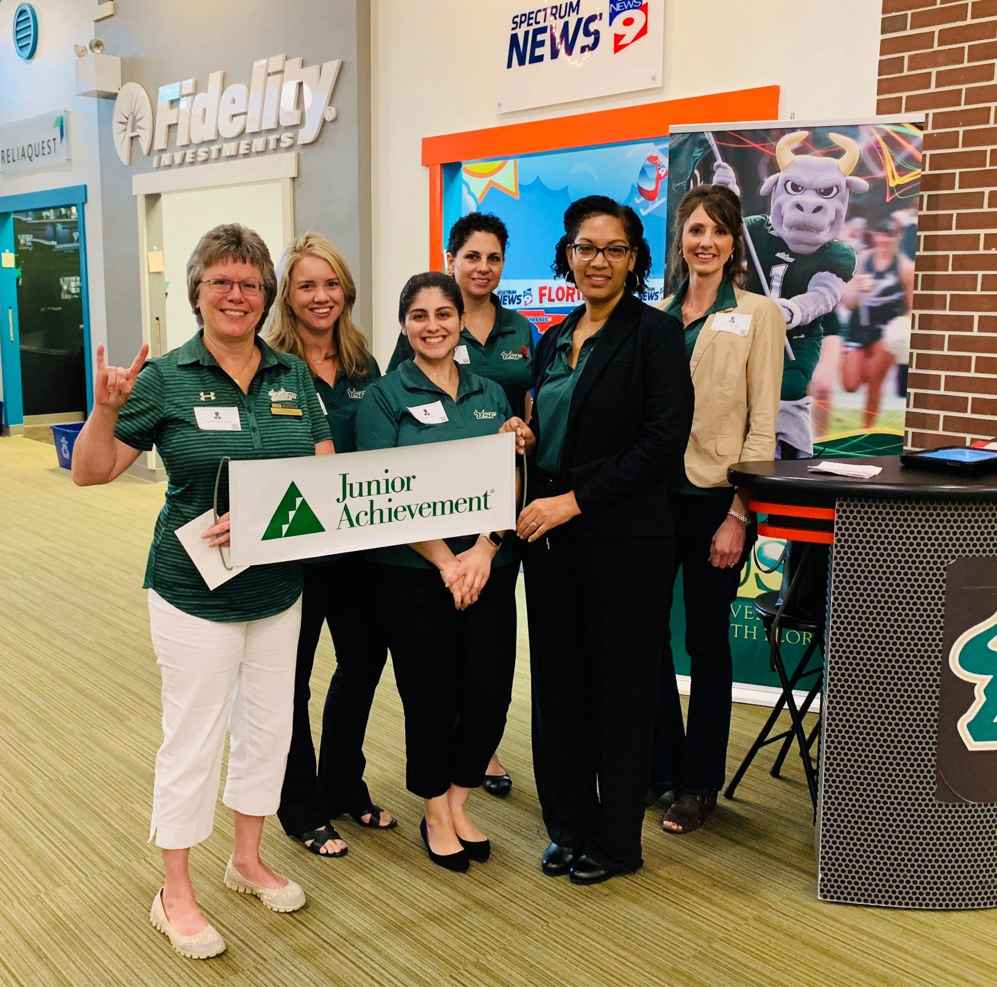 Group photo of Administrative Services Business Center employees holding a sign that shows the Junior Achievement logo while volunteering at Biztown.