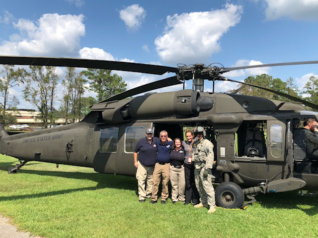 4 Emergency Management professionals alongside an member of the army in front of an army helicopter.