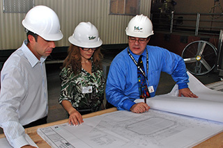 FPC employees studying building plans.