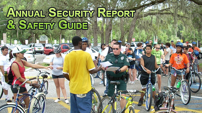 A USF police officer in a green uniform is handing out a report to a group of students with bicycles.
