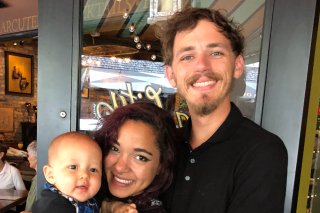 Image shows Connor (CJ) Harris with his family standing in front of a restaurant's glass door