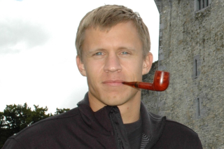 Image shows Scott Simeral with a wooden pipe in his mouth, standing outside in front of a grey castle