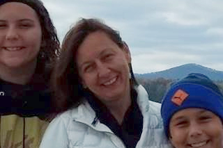 Image shows Michelle Sonnenberg smiling at the camera with her family in front of mountains