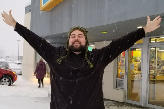 Image shows Mike Stowe, arms oustretched into a Y shape, standing in front of a store as snow falls