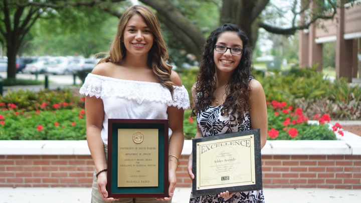 Image shows two women from a past awards ceremony, each holding an award plaque. The backdrop is the alumni center's courtyard garden with a large, shady oak tree, tropical plants, and a number of red flowers.