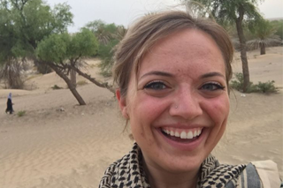 Image shows Cat Modlin-Jackson in outside in Oman, smiling at the camera. Behind her is a sandy landscape with trees growing, some growing diagonally, leaning to the left.