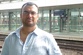 Pablo Brescia is wearing a white shirt and glasses while facing the camera. He is at a train station.