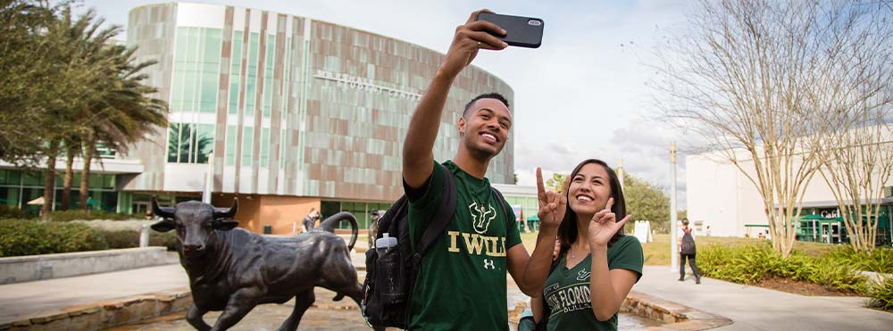 Two USF students are taking a selfie in front of a bull statue at the Marshall Student Center. They are smiling and wearing USF t-shirts.