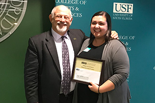 Claudine Boniec is receiving an award from Dean Eric Eisenberg. They are smiling at the camera and standing in front of a green USF backdrop.