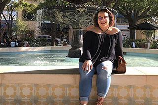 Ennis Cruz Gonzalez is smiling and sitting in front of a fountain. She has short curly hair and is wearing a black shirt and jeans.