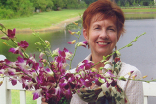 Christine Probes is smiling and holding a bouquet of pink flowers in front of a lake.
