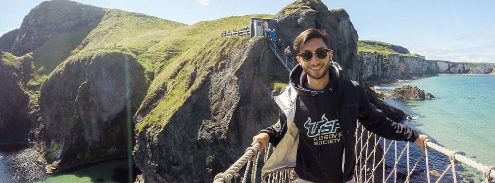 A study abroad student is standing on a rope bridge. He is smiling and wearing a USF sweatshirt.