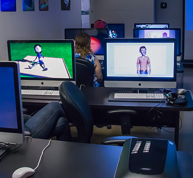 Animation and Digital Modeling Animation - Photo of students viewing 3D animation projects in the School of Art & Art History.
