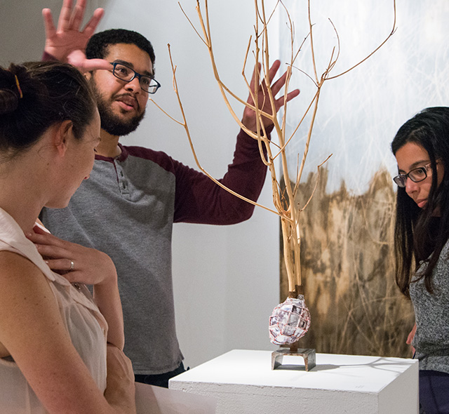 Business and Art - Photo of students viewing and discussing a sculpture during an exhibition.