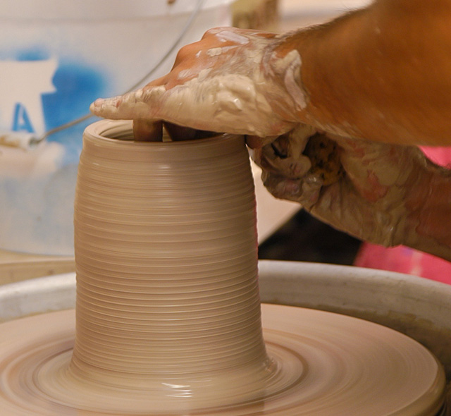 Ceramics - Photo of student shaping a piece of clay on a potter's wheel.