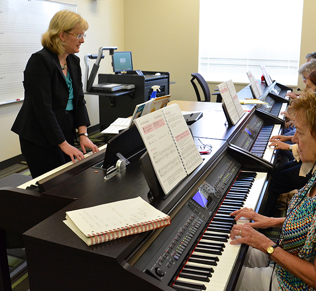 Music Education - Photo of Music Education teacher during a research session with a class of senior citizens attending a piano class.