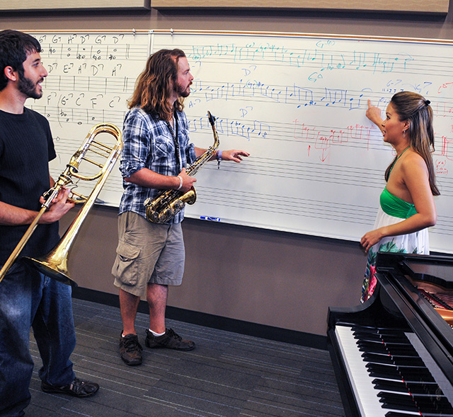 Music Studies - Photo of music students discussing components of a melody in a rehearsal classroom.