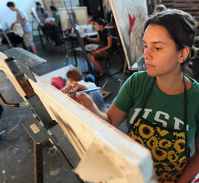 Painting - Photo of an art student focusing on her work while painting on a canvas.