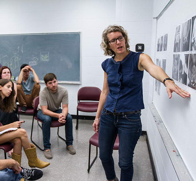 Photography - Photo of an art professor and her students participating in a photography project evaluation in the USF School of Art & Art History.
