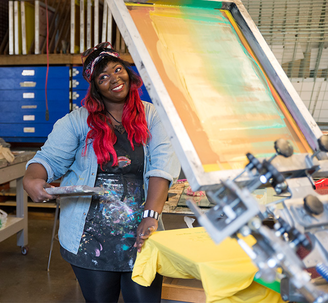 Printmaking - Photo of an art student setting up a t-shirt and silk screen in the printmaking studio.
