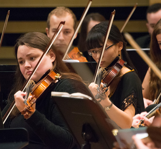 Strings Performance - Photo of violinists reading and playing during performance.
