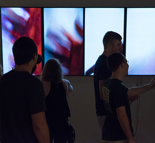 Video - Photo of students interacting with an exhibition display of MFA student video art.