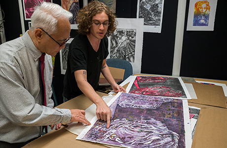 James Moy, Dean of the USF College of The Arts, examining prints inside a student's studio at the USF School of Art & Art History.