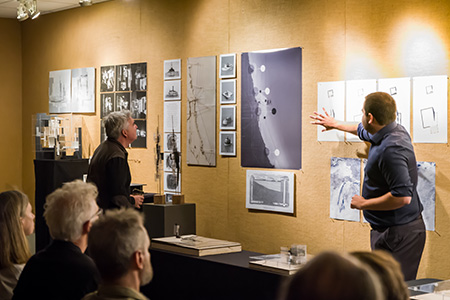 Photo of USF Architecture student presenting his thesis project in front of a review panel.