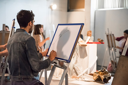 Students in the drawing studio drawing at their easels.
