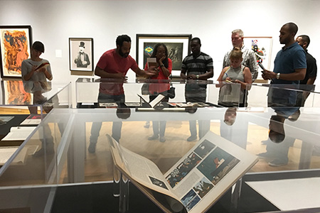 Visitors attend a curator tour of an exhibition at the USF Contemporary Museum to learn about the works on display.