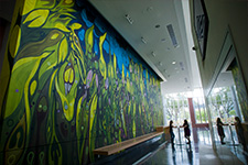 Two students talking in the Music Concert Hall lobby next to the mural by artist Janaina Tschäpe.