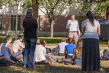 Undergraduate Orientation - Photo of students attending a lecture outdoors on the USF School of Music lawn.