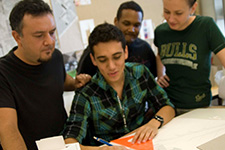 A faculty member helping three architecture students on a paper sketch project.