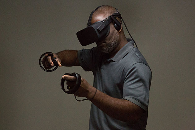 McArthur Freeman wears virtual reality gear with arms raised as he sculpts with virtual reality technology