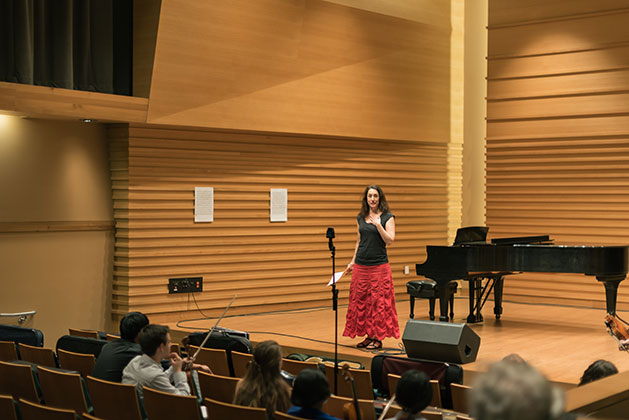 Monica Germino stands on the stage of Barness Recital Hall speaking before students