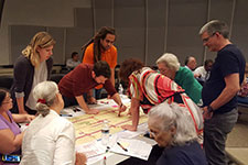 nine people look at community designs on a table at a meeting with FDOT District 7