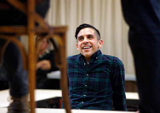 Matthew Lopez looks toward foreground performers on stage while attending a rehearsal for The Inheritance