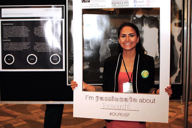Catherine Gomez holds up large instant photo frame prop at the 2017 USF Undergraduate Research and Arts Colloqium