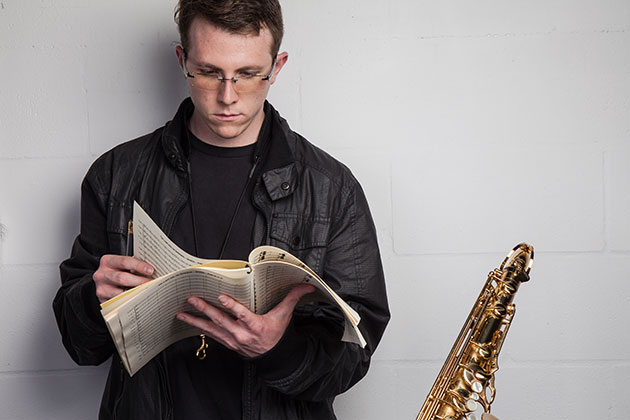 Zachary Bornheimer looks at sheet music in his hands with a saxophone to his left in a studio portait