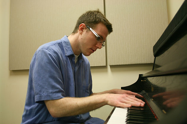 Zachary Bornheimer plays piano in a practice room in the School of Music