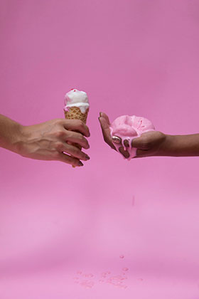 """Protraction"" by Erika Schnur, former USF BFA student. Two hands holding melting icecream against a pink background."