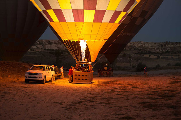 Photo of a hot air balloon with people in it next to a white suv