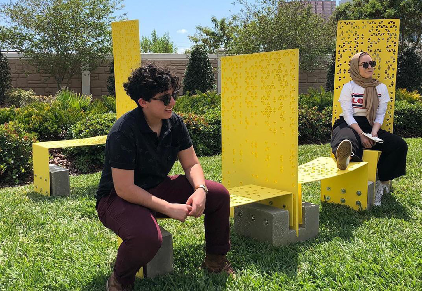 Two people sitting on a vibrant yellow piece designed by USF Architecture students for ENCORE.