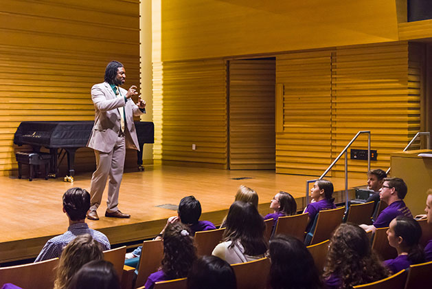 Dr. Dakeyan Graham stands on stage of Barness Recital hall before USF music students