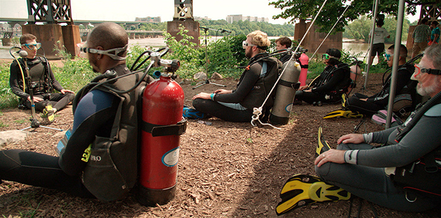 suba divers sit on the ground outdoors