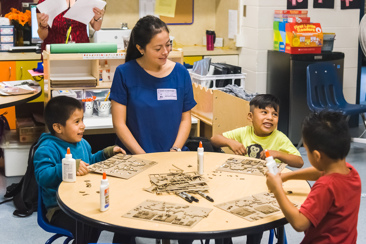 USF architecture student Ana Meneses sits at a table with three VPK students as they build model houses.