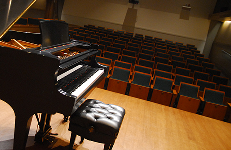 Stage view of grand piano overlooking audience seating.