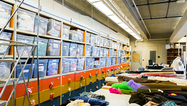 Storage bins containing multiple fabrics and assorted costume-making materials are lined in shelves along one wall of the costume shop. A dress form stands among the tables covered with fabrics and tools.
