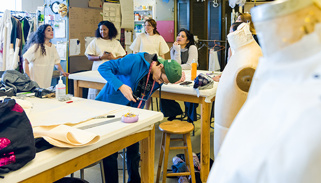 Students working in the costume shop. One student closely examines the costume laid out on the table, he's holding a pair of scissors in one hand.