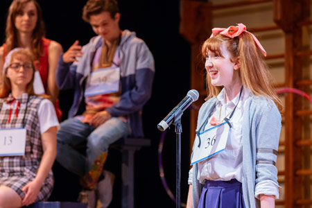 "A student spells a word in front of a crowd in the performance of ""The 25th Annual Putnam County Spelling Bee."""